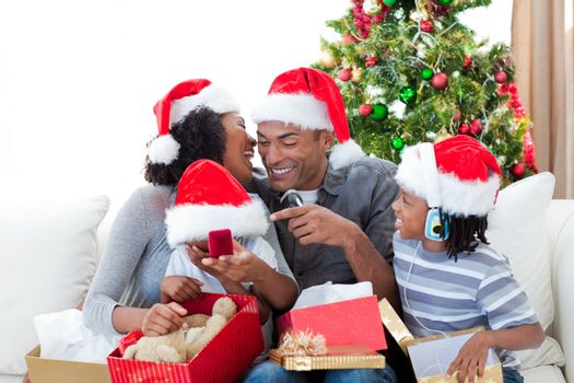 Happy Afro-American family having fun with Christmas presents at home