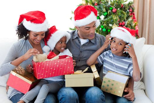 Happy Afro-American family playing with Christmas presents at home
