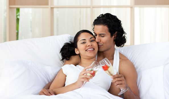 Lover kissing his wife while toasting with Champagne