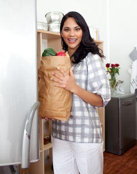 Brunette woman unpacking grocery bag