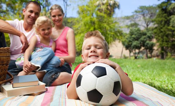 Smiling boy holding a soccer ball with his family in the background