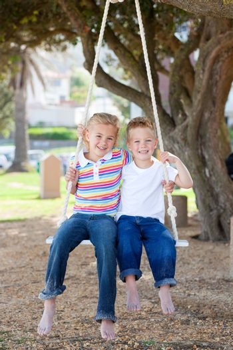 Adorable siblings swinging