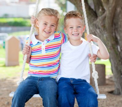 Cute siblings swinging