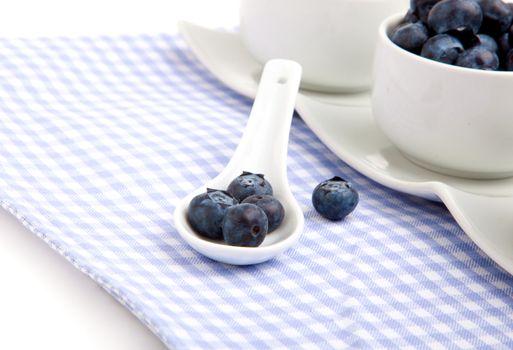 fresh blueberry in white porcelain spoon, on serviette