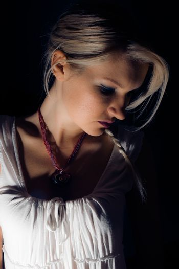 A beautiful blonde girl against a dark background