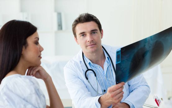 Confident doctors analyzing an x-ray in a meeting