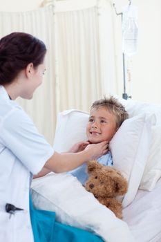 Female doctor checking child throat
