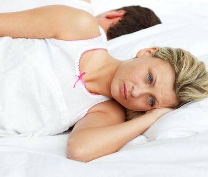 Upset couple in bed sleeping separate