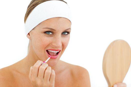 Smiling woman applying gloss