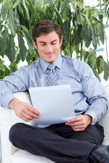 Satisfied businessman reading papers on a sofa