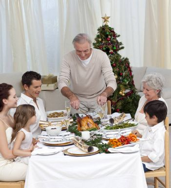 Happy family celebrating Christmas dinner with turkey at home