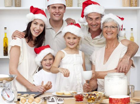 Children baking Christmas cakes in the kitchen with their parents and grandparents