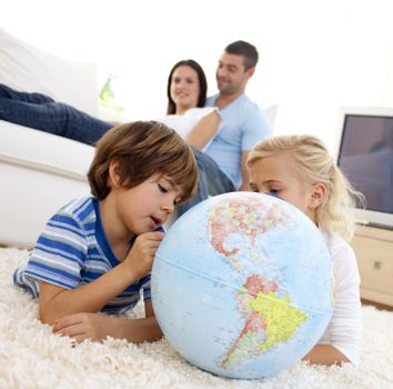 Children playing with a terrestrial globe in living-room with their parents on sofa
