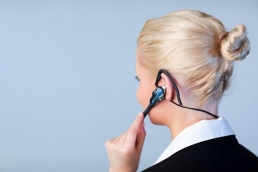 Attractive young businesswoman talking on a headset with focus on headset