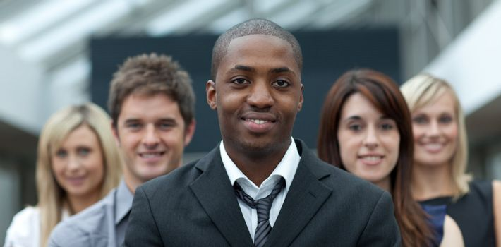 Afro-American young businessman smiling at the camera with his team