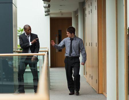 Businessmen saying goodbye in a corridor