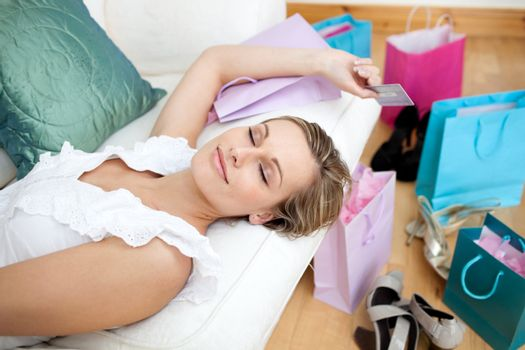 Blond woman relaxing after shopping surrounded with shopping bags  at home