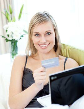 Joyful blond woman shopping on-line sitting on a sofa