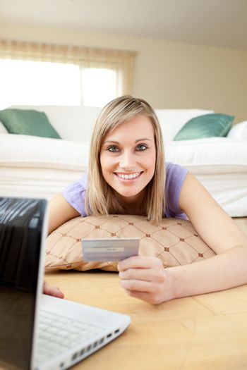 Happy woman shopping on-line lying on the floor