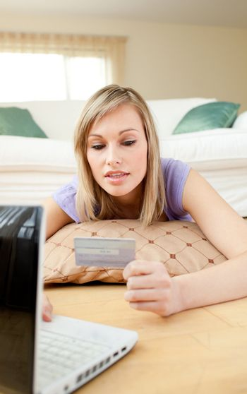 Attractive woman shopping on-line lying on the floor
