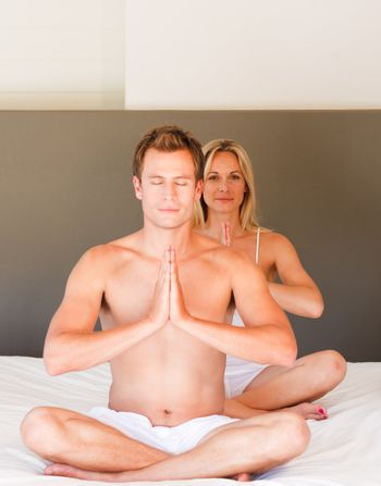Attractive couple doing spiritual exercises on bed