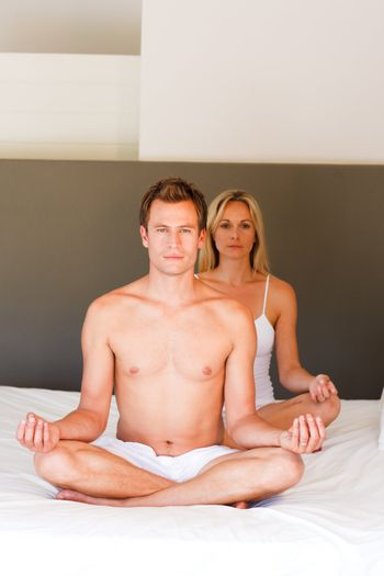 Young couple doing yoga on bed with copy-space