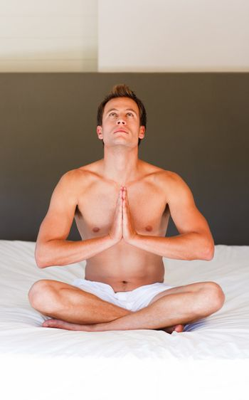 Young boy doing spiritual exercises on bed