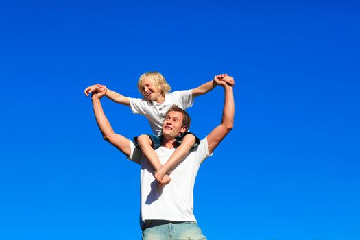 Youth sitting on his father's shoulders