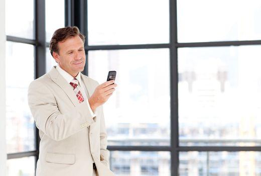 Senior businessman sending an sms with copy-space