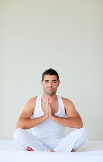 Man sitting on bed meditating with copy-space
