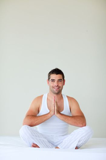 Young man meditating in bed with copy-space