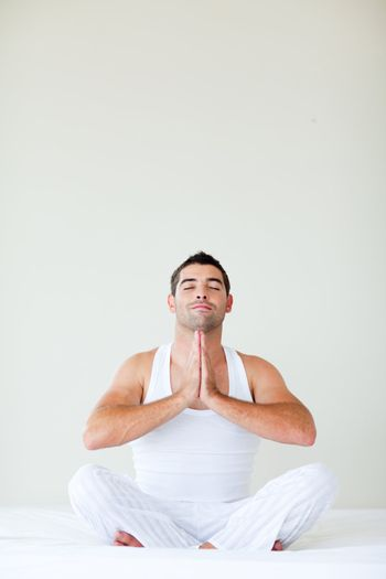 Man sitting on bed doing yoga with copy-space