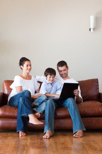 Parents and son playing with a laptop with copy-space
