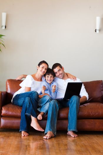 Family using a laptop with thumbs up and copy-space