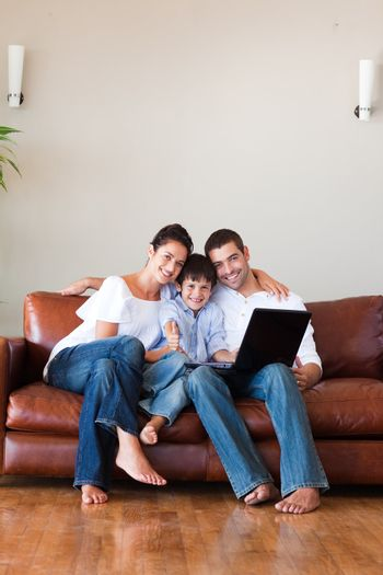 Parents and kid using a laptop with thumbs up and copy-space
