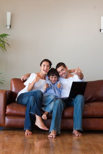 Parents and kid having fun with a laptop and copy-space