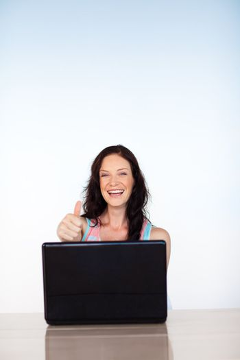 Woman using her laptop with thumbs up and copy-space