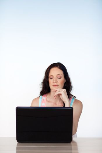 Serious woman working with her laptop with copy-space