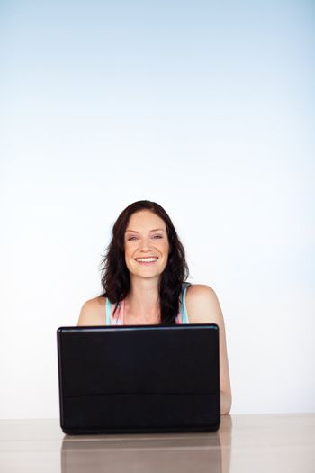 Smiling girl using a laptop with copy-space