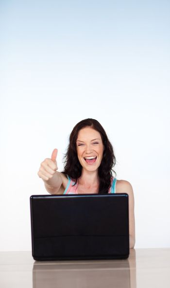 Happy smiling woman using her laptop with copy-space