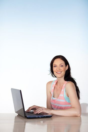 Brunette woman working with a laptop and copy-space