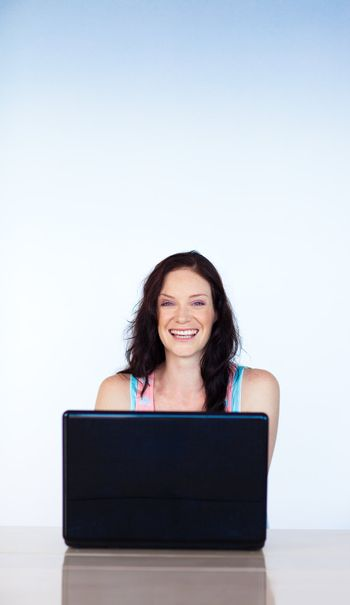 Smiling woman working with a laptop with copy-space