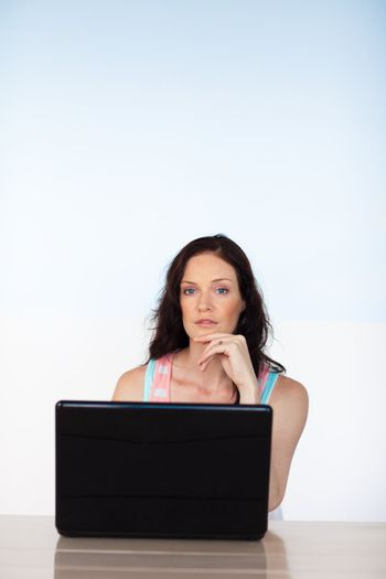 Woman using her laptop looking at the camera with copy-space
