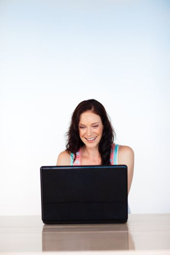 Smiling woman using a laptop with copy-space