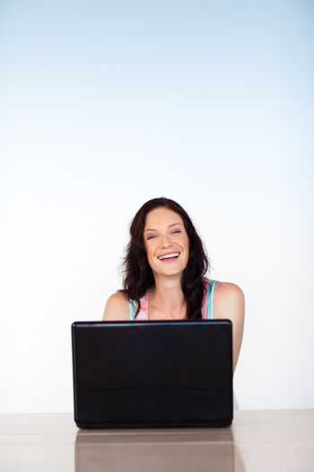 Happy woman working with a laptop with copy-space