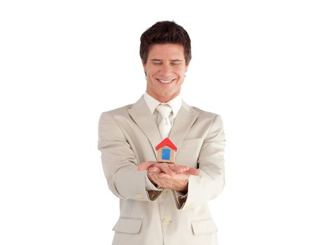 Good-looking businessman holding a house