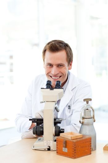 Male scientist looking through a microscope with copy-space