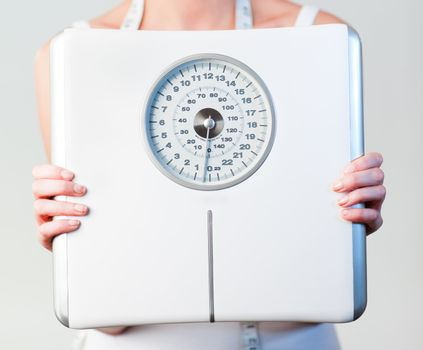 Close-up of a woman holding a scales with focus on scales