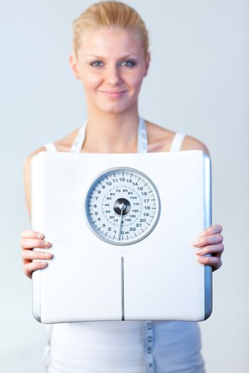 Friendy woman holding a scales with focus on scales