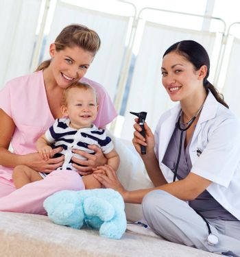 Baby with pediatrician and nurse in hospital smiling at the camera